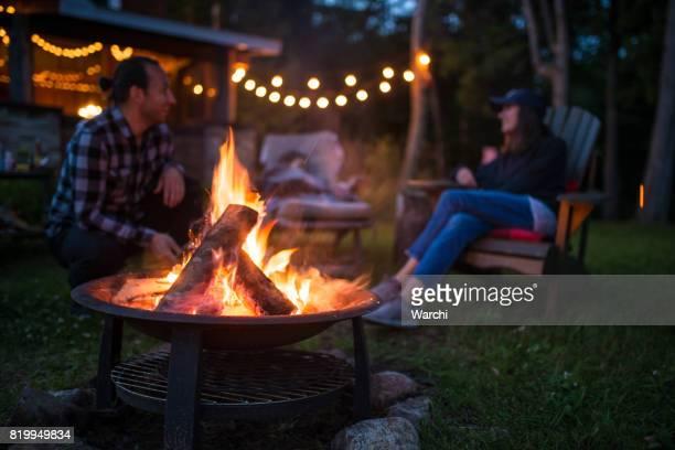 若い家族はキャンプファイヤーの近く美しいカナダ シャレーでは夜遅くに地球温暖化します。