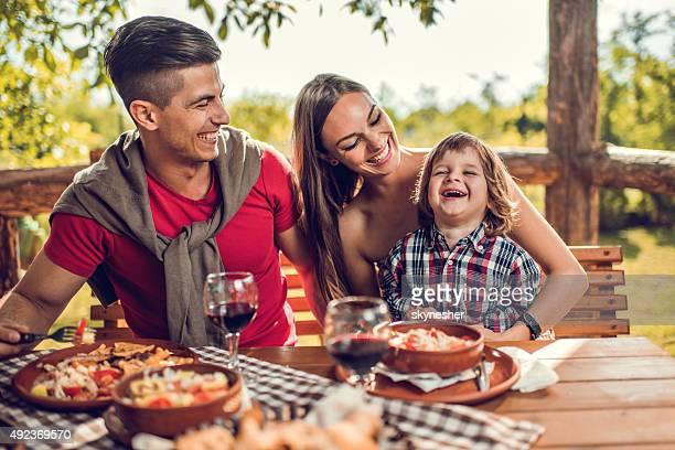 Jeune famille rire lors d'un déjeuner au restaurant.