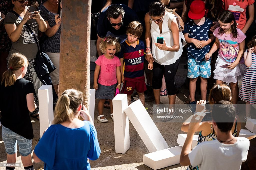 A young family look on as large domino pieces collapse during the Arts Centre Melbournes Dominoes arts project in Melbourne, Australia February 6, 2016. More than 7000 giant dominoes snaked through Melbourne city over 2km.