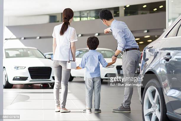 Young family looking at new car in showroom