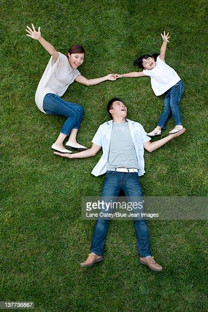 Young family lying down and playing on the grass