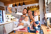 Beautiful young family making cookies at home. Father, mother. toddler boy and baby taking selfie with a smartphone.