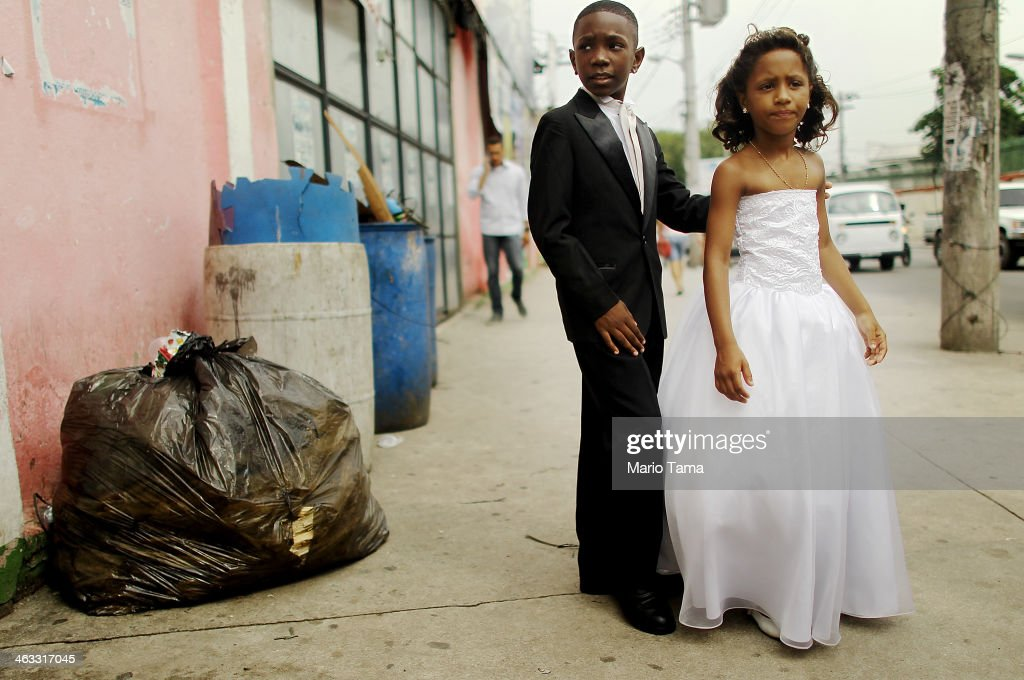 Young family members wait to enter a communal marriage ceremony in the Jacarezinho pacified community, or shantytown, on January 17, 2014 in Rio de Janeiro, Brazil. The 'favela' was previously controlled by drug traffickers and is now occupied by the city's Police Pacification Unit (UPP). The UPP hosted the communal wedding for 18 couples to mark the first anniversary of the UPP occupation of the community. In Brazil, weddings are costly and couples sometimes join communal weddings to save costs. The UPP are patrolling some of Rio's favelas amid the city's efforts to improve security ahead of the 2014 FIFA World Cup and 2016 Olympic Games.