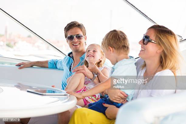 young family of four having fun on their yacht