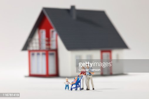 A young family of miniature figurines in front of a house