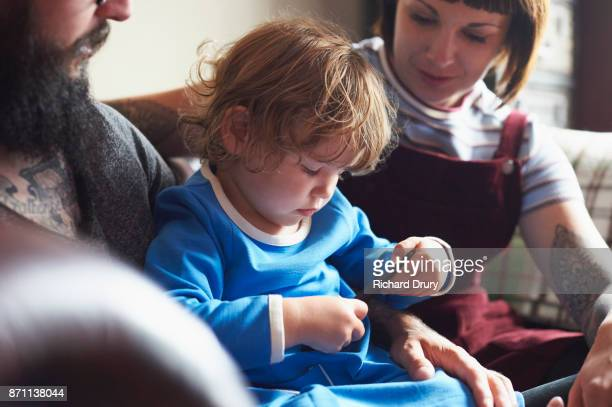 Young family on sitting their sofa with toddler girl using smartphone