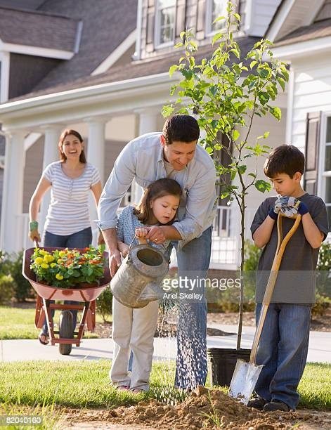 Young Family Planting Tree in Front of House