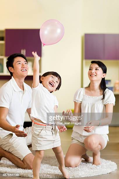 Young family playing balloon