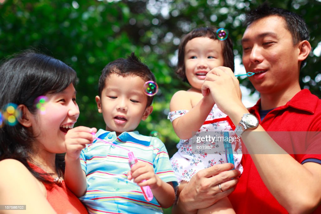 young family playing bubble in the garden