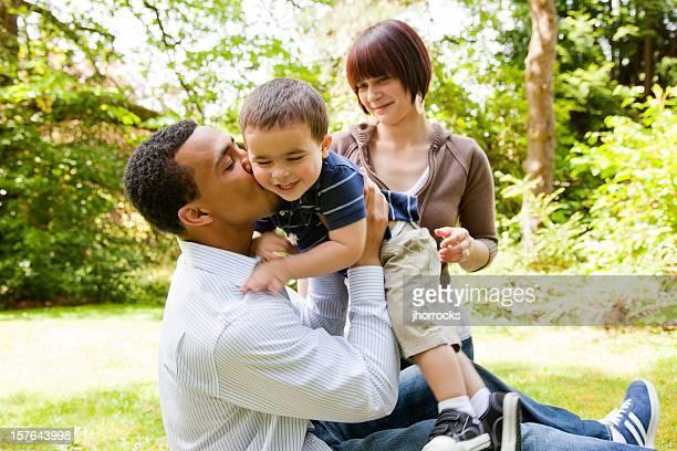 若い家族の公園で遊ぶ