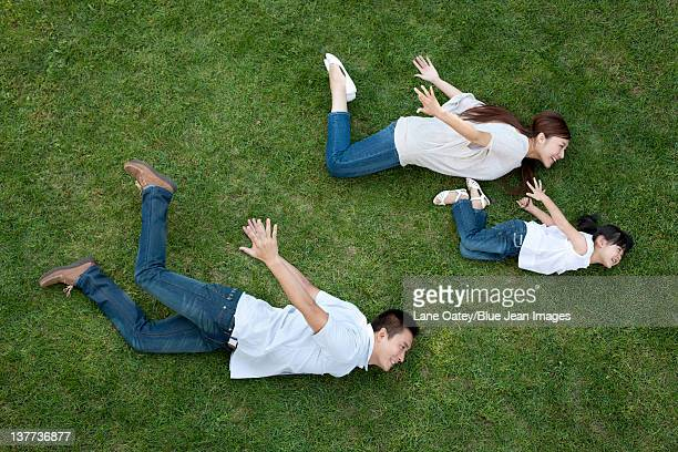 Young family playing on the grass pretending to fly