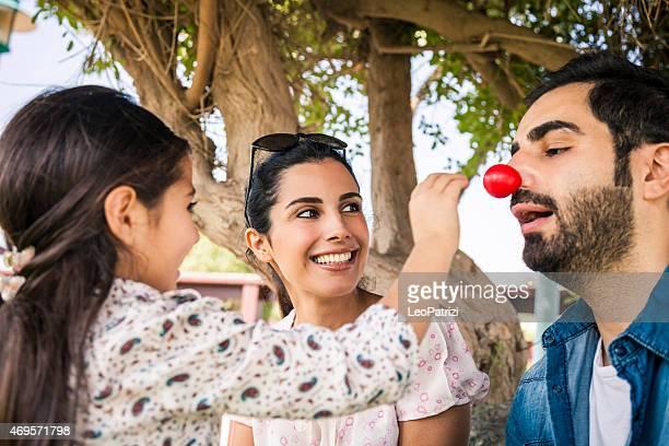 Junge Familie spielen mit einem roten clown Nase