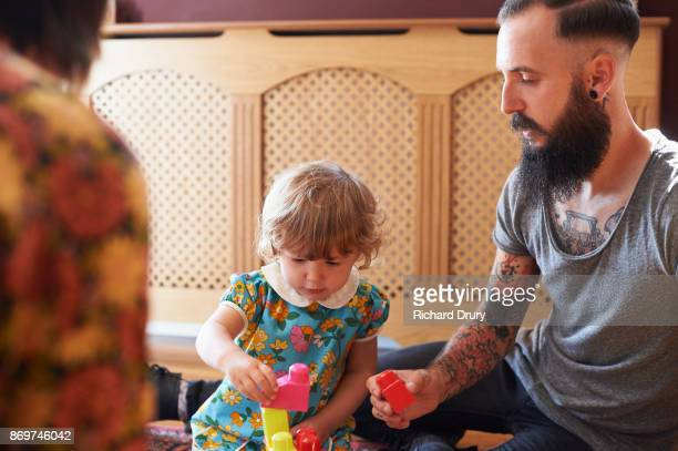 Young family playing with building blocks