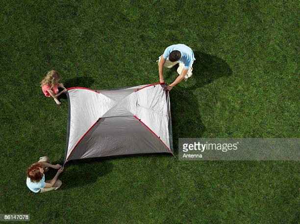 A young family putting up a tent