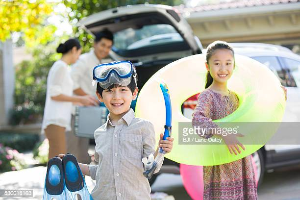 Young family putting water sports equipment into the car