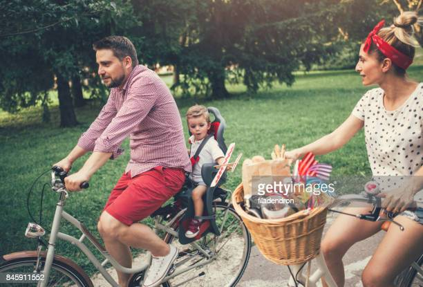 Young family riding bicycles in the park