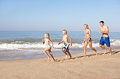 Young family running on beach