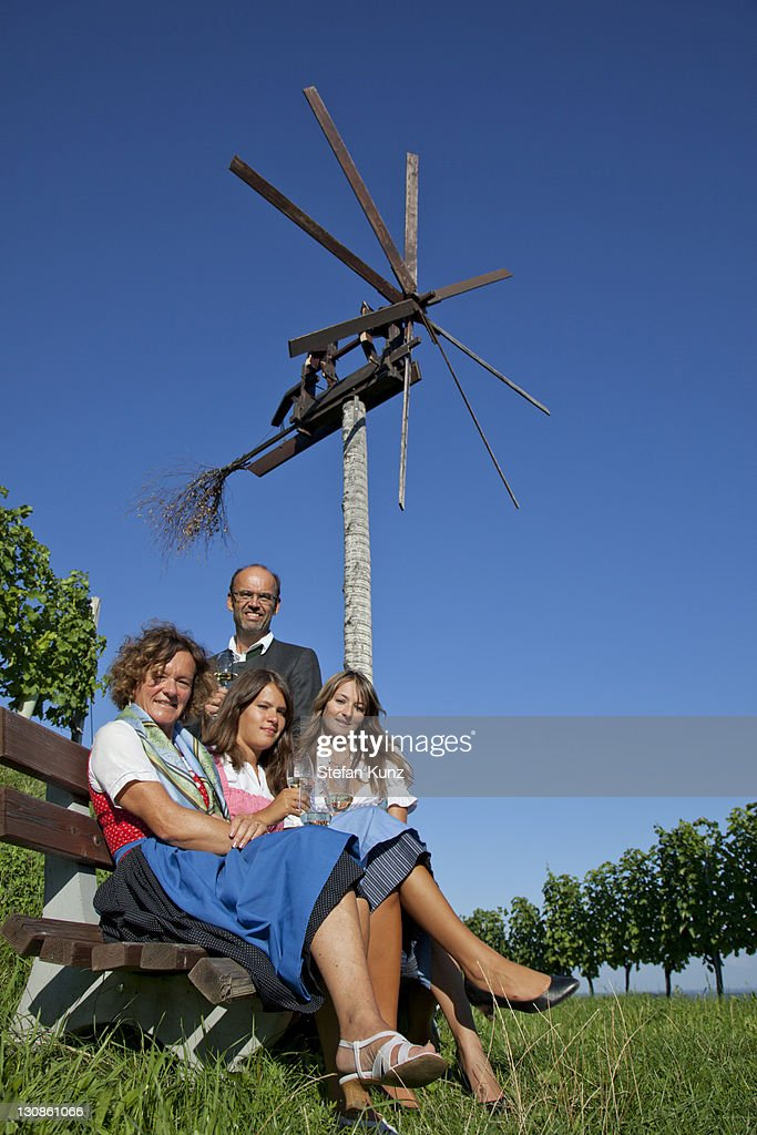 Young family sitting in front of a Klapotetz, a wind-rattle scarecrow, Southern Styria, Styria, Austria, Europe : Stock Photo