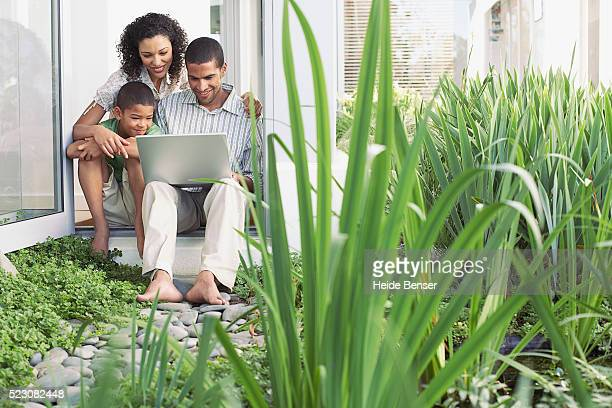 Young family sitting in yard using laptop