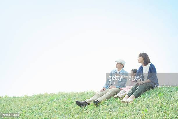 Young family sitting on a hill