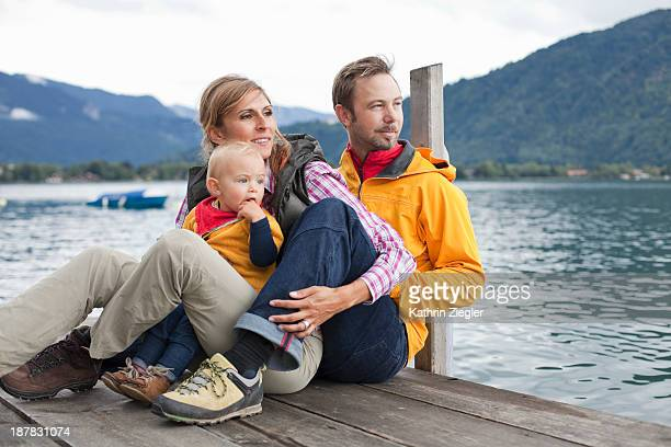 young family sitting on jetty at mountain lake