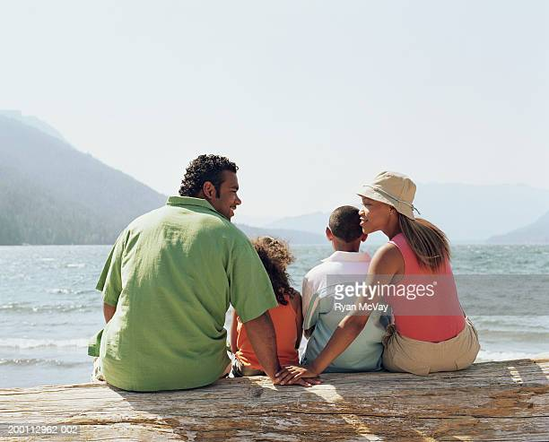 Young family sitting on log overlooking lake, rear view
