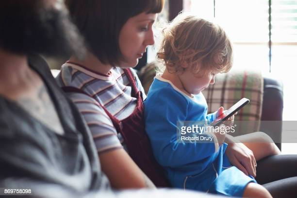Young family sitting on their sofa, daughter using smartphone