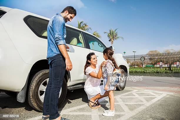 Young family taking daughter to school by car