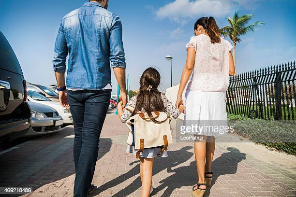 Young family taking daughter to school