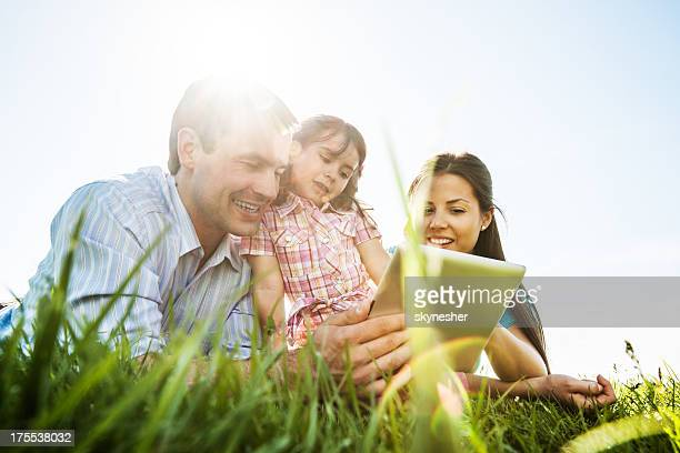 Young family using a digital tablet in the park.