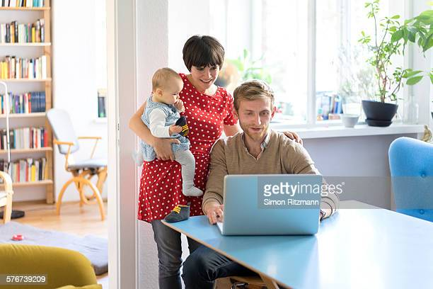 Young family using laptop at home.
