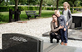 Young mother with kids visiting the grave at graveyard of deceased husband or grandparent