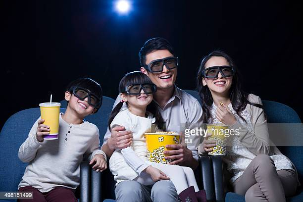 Young family watching 3D movie in cinema