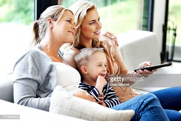 Jeune famille regarder la télévision à la maison