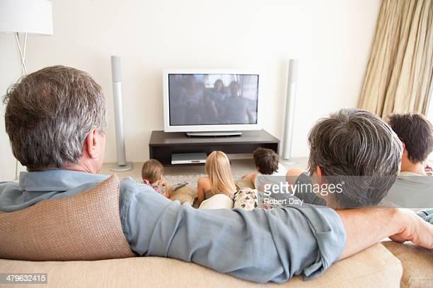 Eine junge Familie vor dem Fernseher mit Großeltern