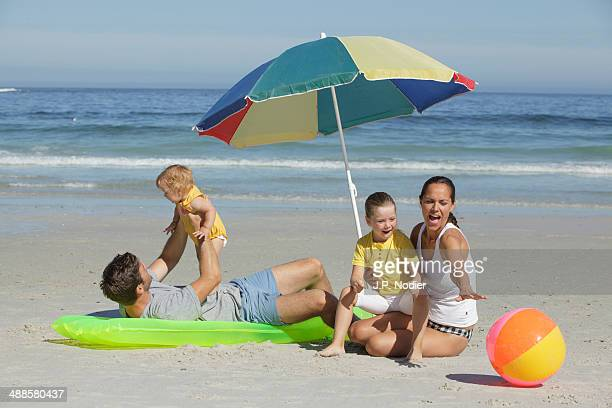 Young family with 2 children sitting on beach
