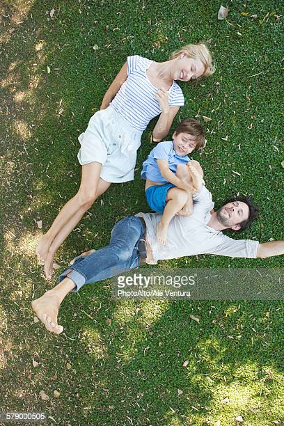 Young family with boy lying together on grass