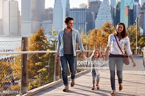 Young family with daughter taking a walk on footbridge : Stock Photo