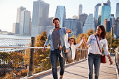 Young family with daughter taking a walk on footbridge