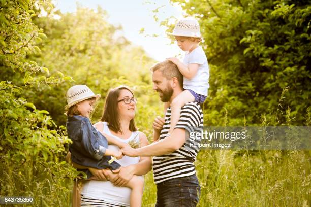 Young family with little daughters in sunny summer nature.