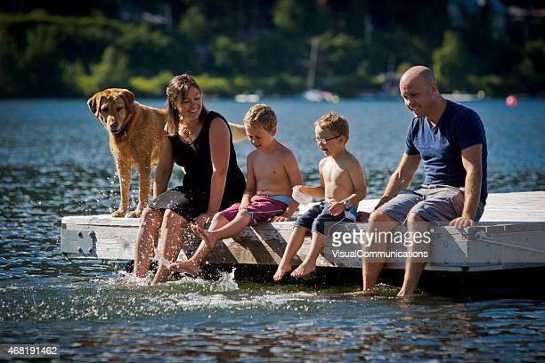 Junge Familie mit Hund sitzend am dock am See.