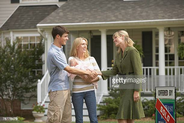 Young Family with Real Estate Agent in Front of New House