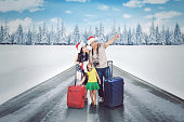 Young family wearing Santa hat while looking at snows and standing with suitcases on the highway