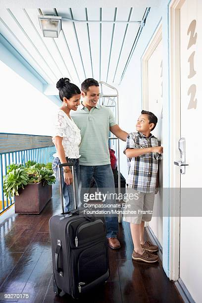 Young Family with suitcases, opening hotel door.