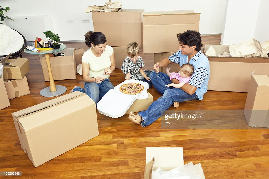 Young family with two children eating pizza in new apartment