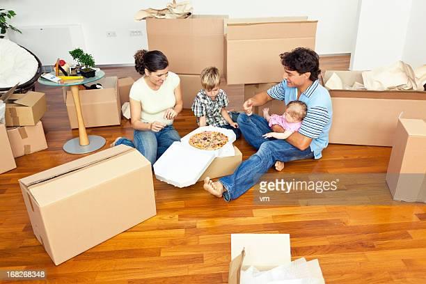 Giovane famiglia con due bambini mangiando pizza nel nuovo appartamento