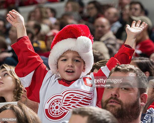 A young fan cheers for his team with his Christmas hat during an NHL game between the Detroit Red Wings and the Nashville Predators at Joe Louis...