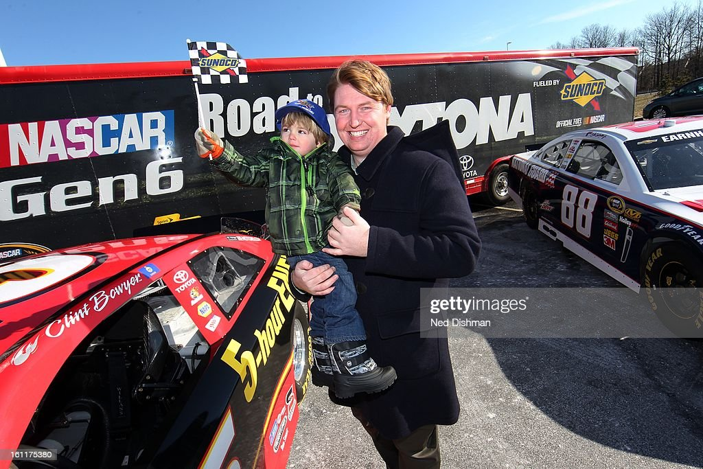 A young fan displays giveaways with his father during a Road to Daytona Fueled By Sunoco Tour stop at the Sunoco Station on February 9, 2013 in Newark, Delaware.