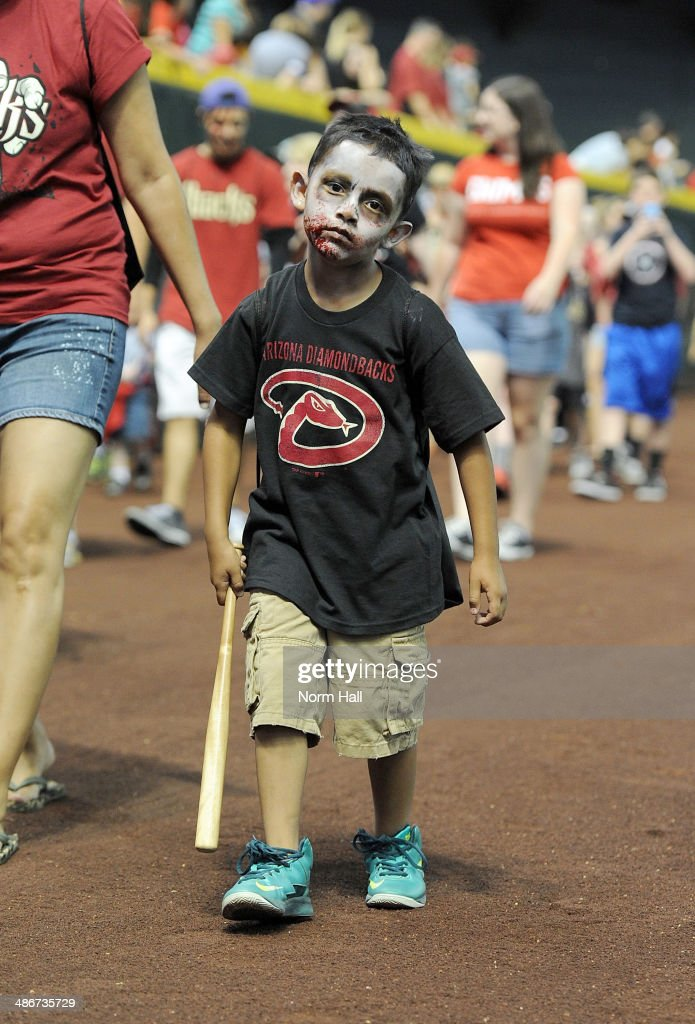 A young fan dressed like a zombie walks on the warning track prior to a game between the Arizona Diamondbacks and the Philadelphia Phillies at Chase Field on April 25, 2014 in Phoenix, Arizona.