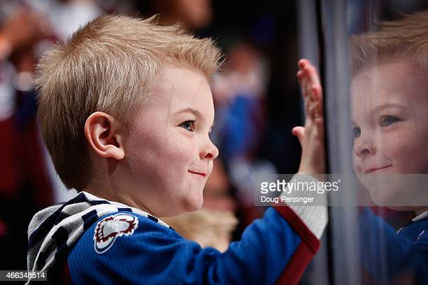 A young fan gets a view from the glass as the Colorado Avalanche warm up to face the Calgary Flames at Pepsi Center on March 14 2015 in Denver...